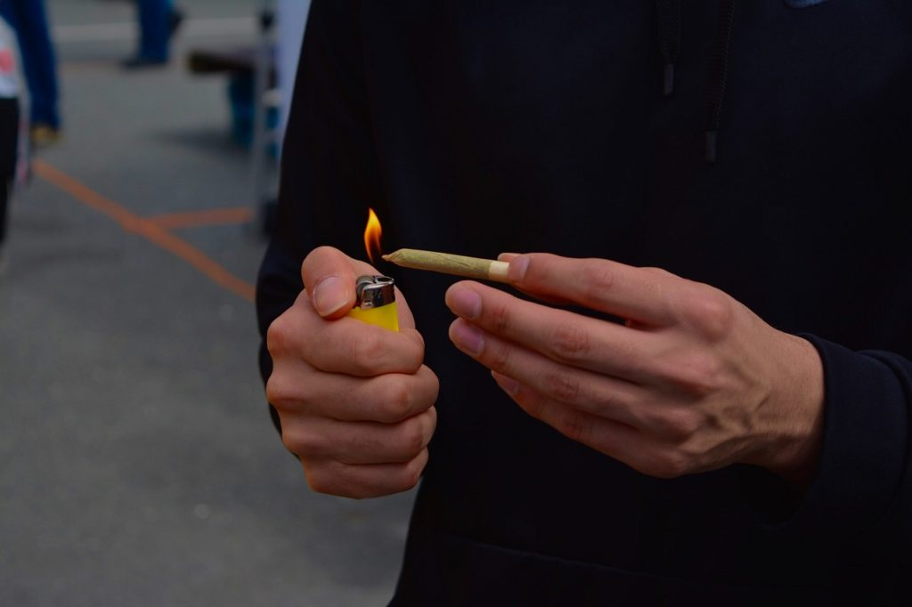 someone lighting a joint representing the cannabis stock exchange